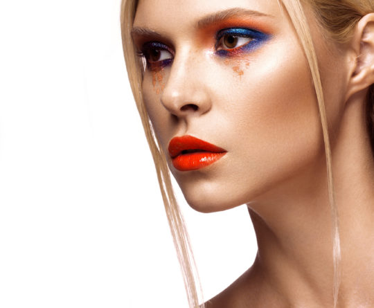 Beautiful girl with bright colored makeup and orange lips. Beauty the face. Photos shot in studio