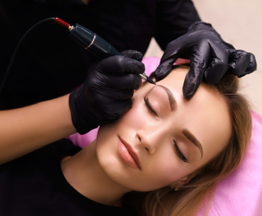 Cosmetologist applying permanent make up on eyebrows- eyebrow tattoo.